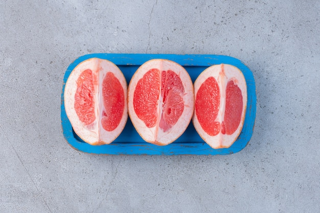 Grapefruit slices on a small blue platter on marble background.