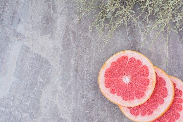 Grapefruit slices on stone background with plant.