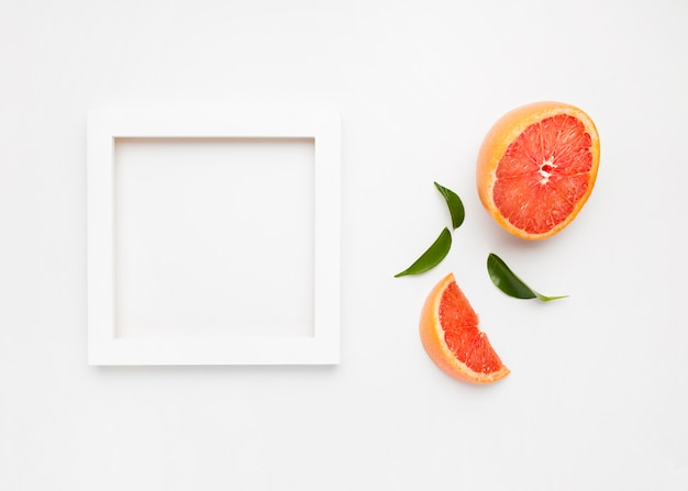 Grapefruit and slices with leaves isolated on white surface