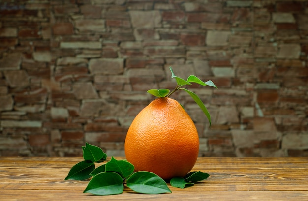 Grapefruit with leaves side view on wooden and brick stone background