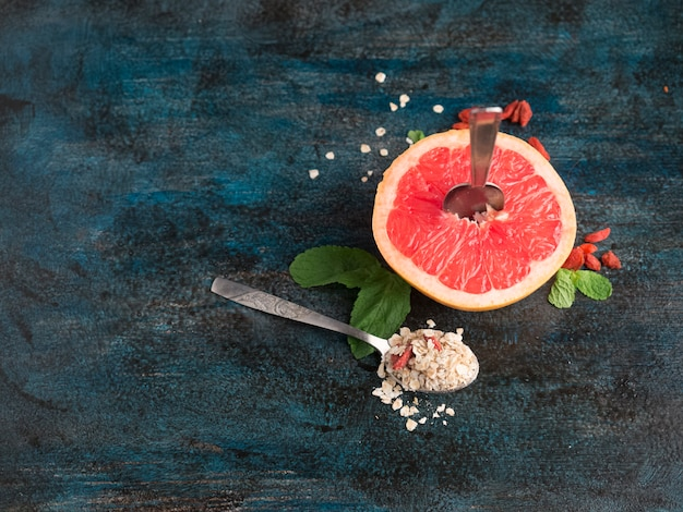 Grapefruit with oatmeal in spoon on table