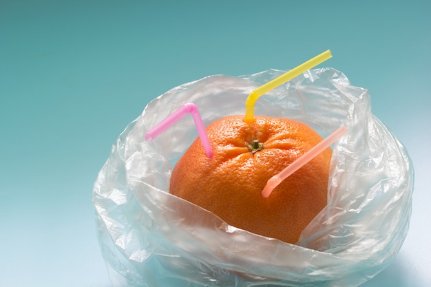 Grapefruit with plastic straws in a plastic bag