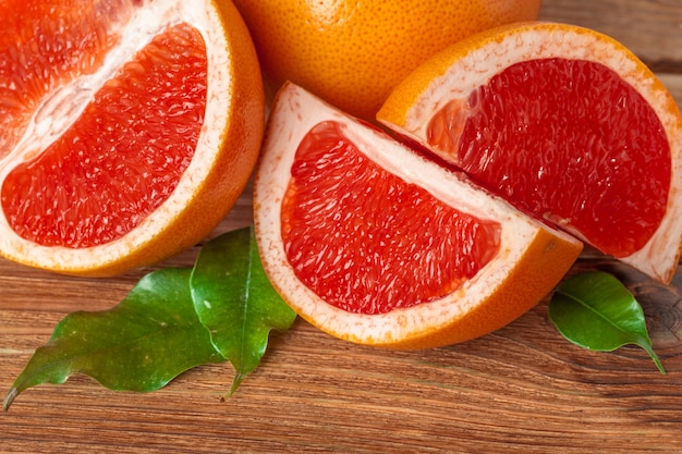 Grapefruit with slices on a wooden table.