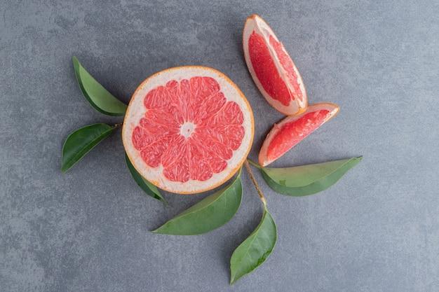 Грейпфруты и листья на серой поверхности