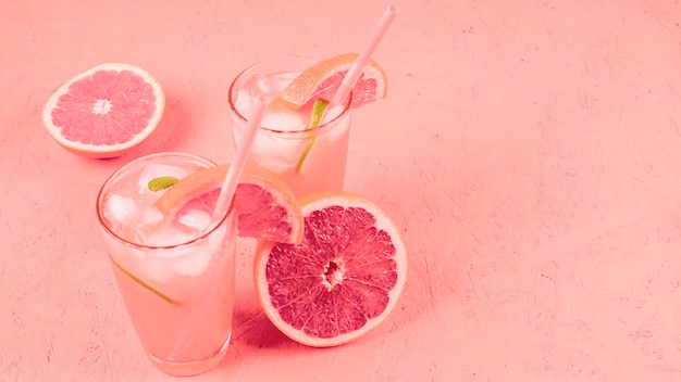 Grapefruits cocktail with fruit slices and ice cubes on coral textured background