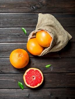 Грейпфруты в мешке на черном деревенском столе