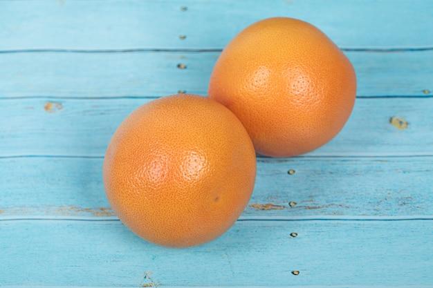 Грейпфруты на деревенском синем деревянном столе