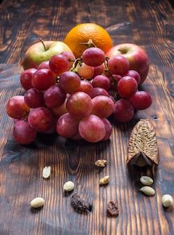 Виноград и фрукты на старом деревянном фоне