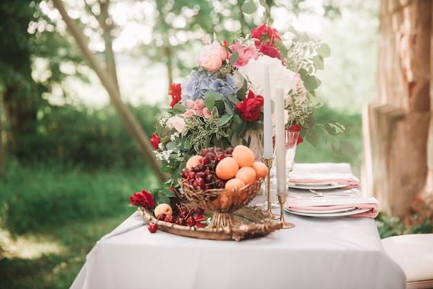 休日のテーブルの上の果物の花瓶のブドウと桃