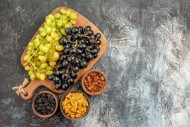 Grapes appetizing bunches of grapes on the wooden board bowls of dried fruits