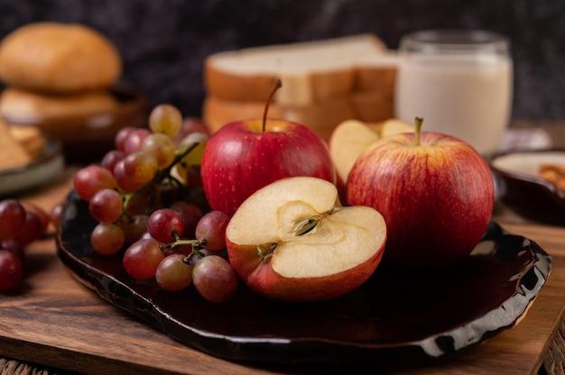 テーブルの上の皿にブドウ、リンゴ、パン