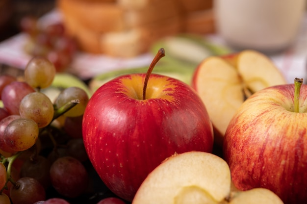 Grapes, apples and bread in a plate on the table