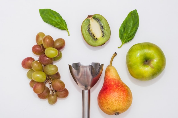 Grapes; basil; kiwi; apple and pear with electric hand blender on white background