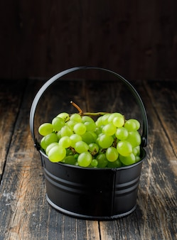 Grapes in a black basket on a wooden surface. side view.