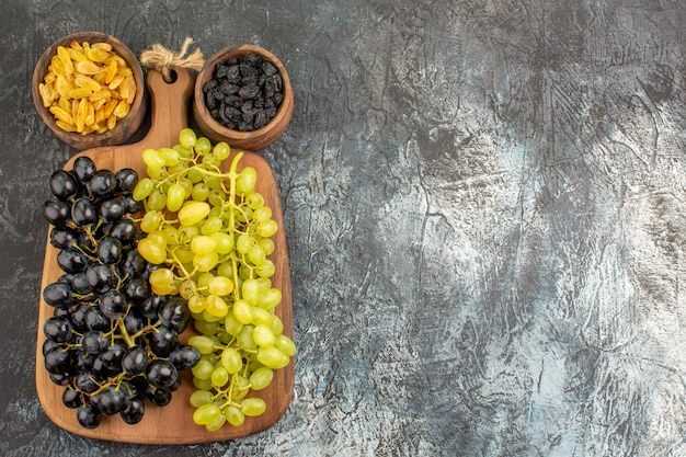 Grapes bunches of grapes on the wooden board between two bowls of dried fruits
