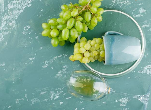 L'uva in una tazza con la bevanda piana giaceva sul gesso e sullo sfondo del vassoio