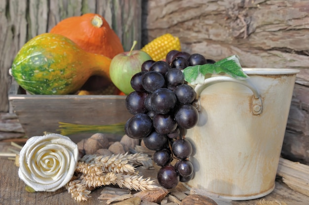 Grapes on decorative bucket and pumpkins background on rustic decor