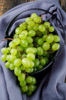Виноград в ведре на деревянной поверхности. плоская планировка