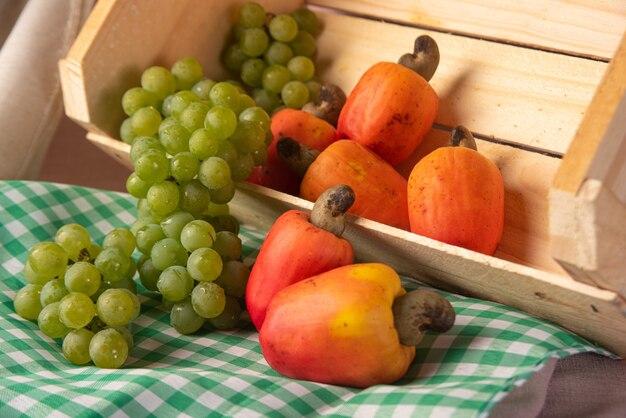 Виноград в деревянном ящике и кешью на фоне ткани, низкая глубина резкости