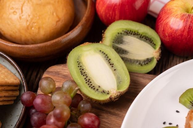 テーブルの上のブドウ、キウイ、リンゴ、パン