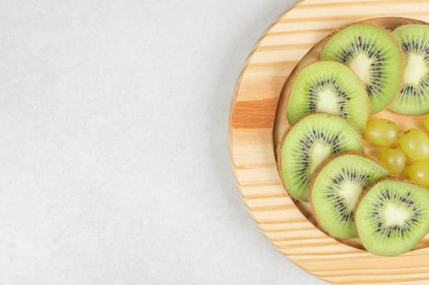 Fette di kiwi e uva sul piatto di legno