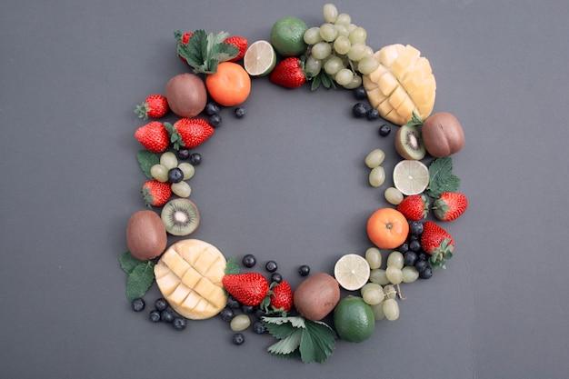 Grapes, mango, strawberry, blueberry, kiwi, mint, lime, citrus fruits on blue background.
