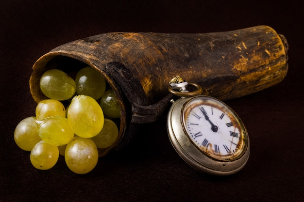 Grapes in an old horn and antique clock.