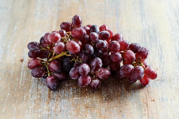 古い木製のテーブルのブドウがクローズアップ
