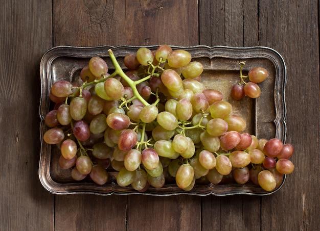 Виноград на серебряном подносе, вид сверху на деревянный стол