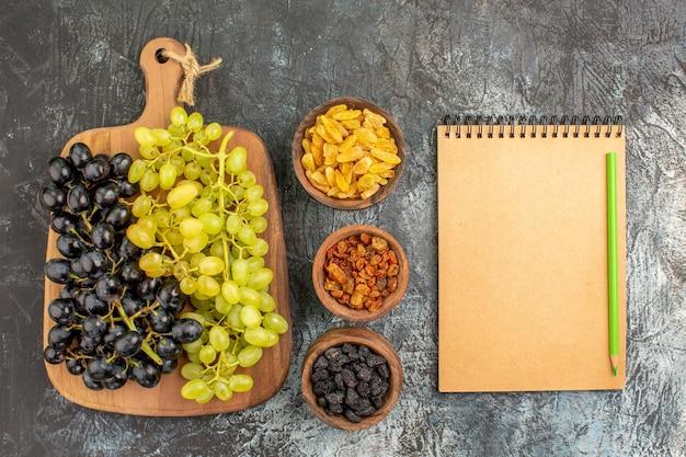 ドライフルーツのおいしいブドウのボウルのブドウ鉛筆ノートの束