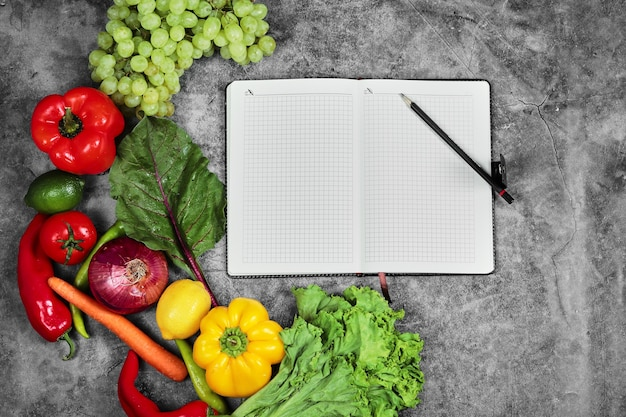 Grapes, peppers, greens, lemon, tomato and empty notebook on marble background.