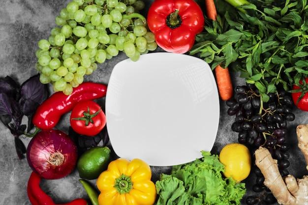 대리석 배경에 포도, 고추, 채소, 레몬, 토마토, 생강, 흰색 접시.