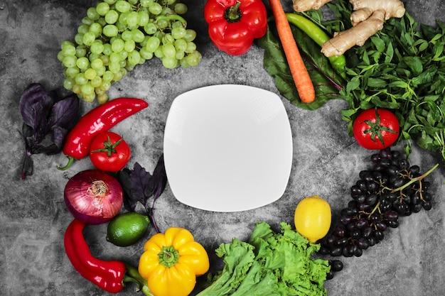Uva, peperoni, verdure, limone, pomodoro, zenzero e piatto bianco su fondo di marmo.