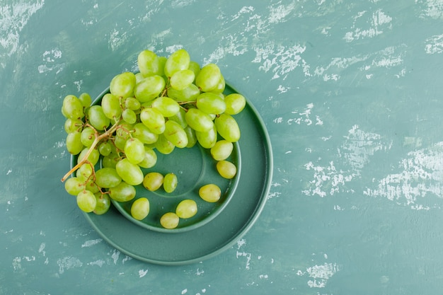 Grapes in saucer and plate flat lay on a plaster background