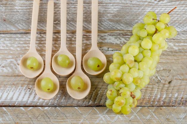 Uva in cucchiai su sfondo di legno, piatto laici.