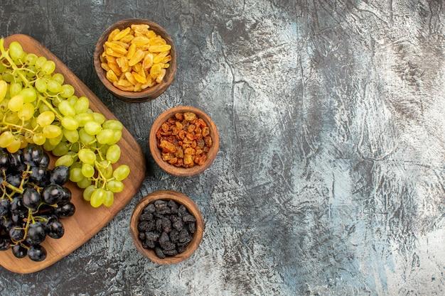 食欲をそそるドライフルーツのブドウボード上のおいしい緑と黒のブドウ