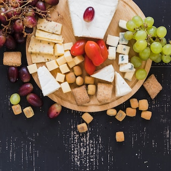 Grapes, tomatoes, cheese blocks and cherry tomatoes on wooden board over the textured