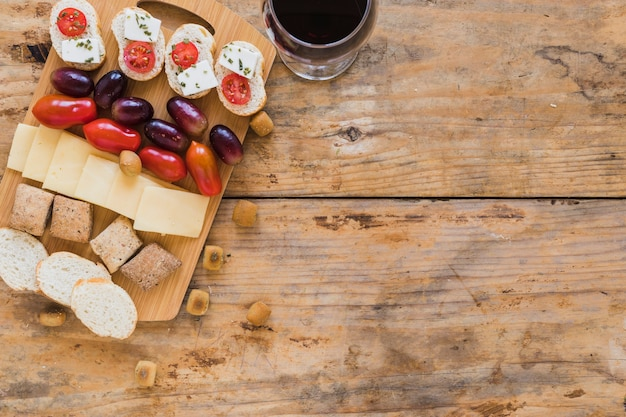 Grapes, tomatoes, cheese slices, bread and pastries with wineglass on wooden desk