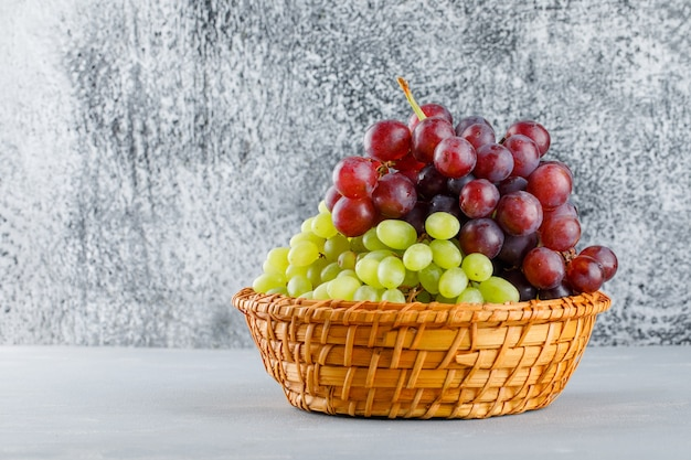 Grapes in a wicker basket on grungy grey and plaster.