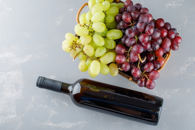 Grapes with drink bottle in a basket on plaster, flat lay.