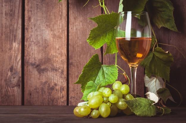 木の背景に葉とグラスワインとブドウ