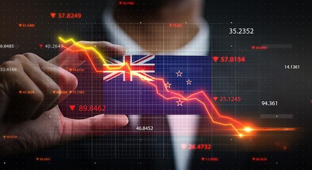 ニュージーランドの旗の前で落ちるグラフ。危機の概念