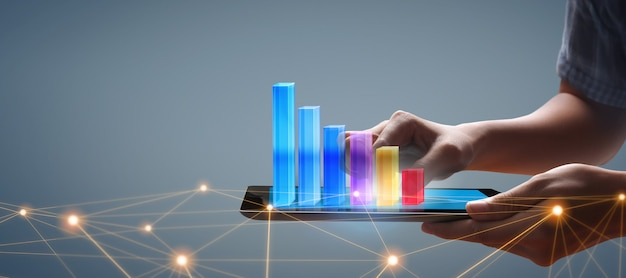 彼のビジネスにおけるグラフの成長とチャートのポジティブな指標の増加、タブレットを手に