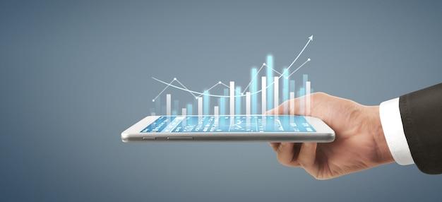 グラフの成長と彼のビジネスにおけるチャートのポジティブな指標の増加、タブレットを手に