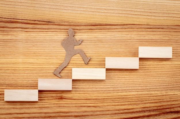 График или деревянные ступеньки на деревянном фоне. концепция целей стратегии успеха в бизнесе.