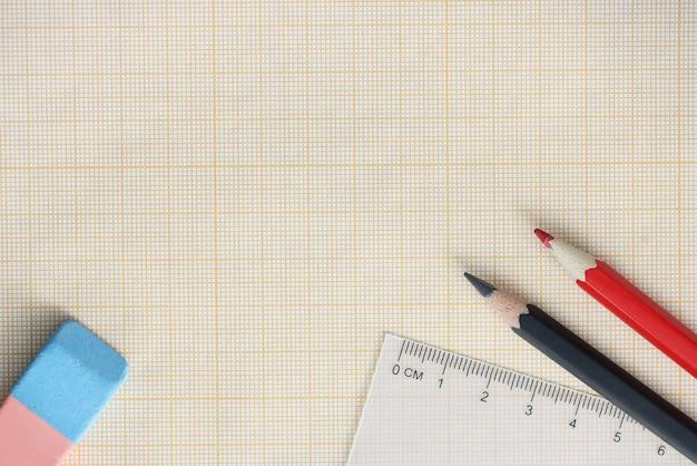 연필과 눈금자가있는 그래프 용지 테이블에 누워
