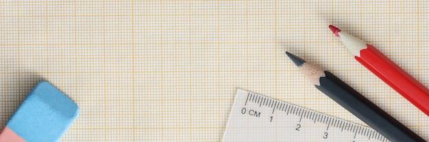 Миллиметровая бумага с карандашами и линейкой лежит на столе