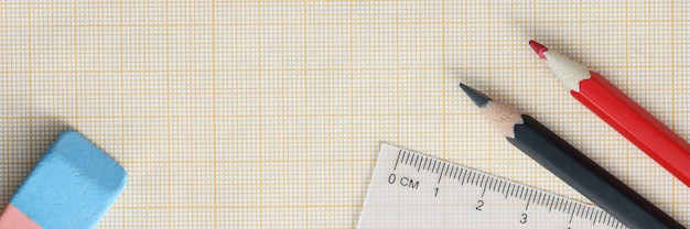 Graph paper with pencils and ruler lie on table