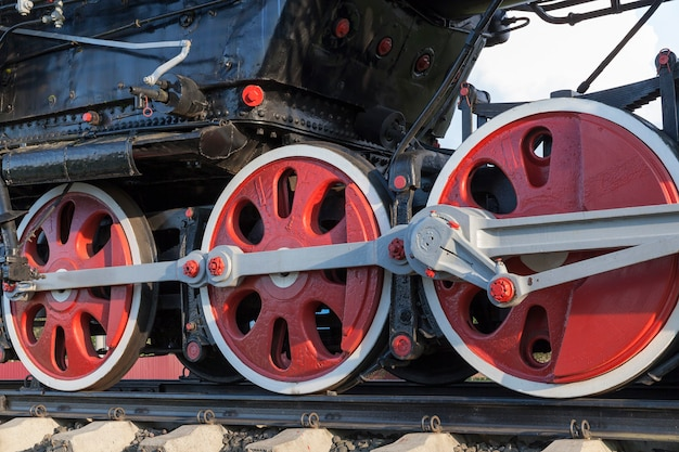 Graphed close up an old steam locomotive wheels with black painted in red. the  was taken up in red.