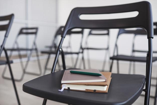 Графическое фоновое изображение ручки и ноутбука на черном стуле в аудитории на бизнес-конференции, копией пространства